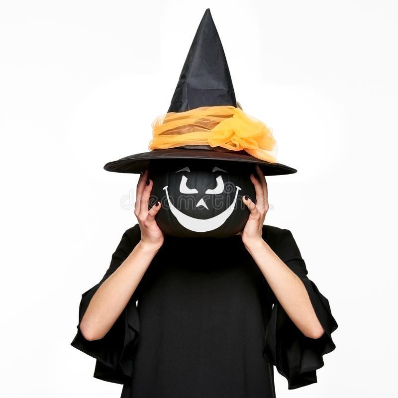 Young woman in witches hat and costume holding pumpkin in front of her face. Halloween Witch with scary face Jack o Lantern. stock photos