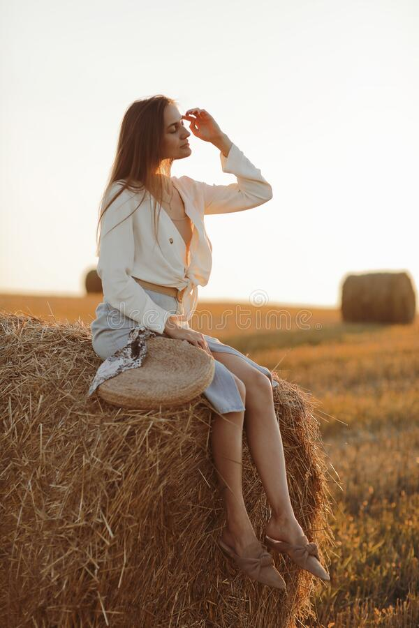 Free Young Woman With Long Hair, Wearing Jeans Skirt, Light Shirt And Straw Bag In Hand, Sitting On Bale On Field In Summer. Female Royalty Free Stock Photos - 216803858