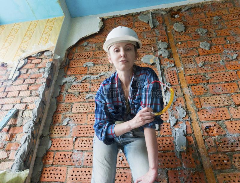Young woman in work clothes in a protective helmet and with safety glasses in her hands stands next to a brick wall stock image