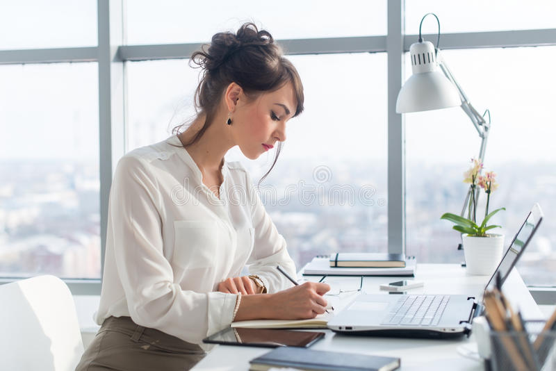 Young woman working as an office manager, planning work tasks, writing down her schedule to planner at the workplace. Young woman working as an office manager royalty free stock images