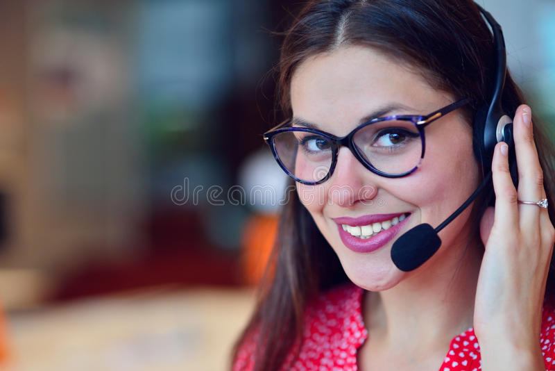 Young woman working in call centre. Surrounded by colleagues royalty free stock images