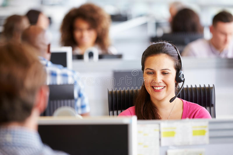 Young woman working in call centre, surrounded by colleagues. Young women working in call centre, surrounded by colleagues royalty free stock image