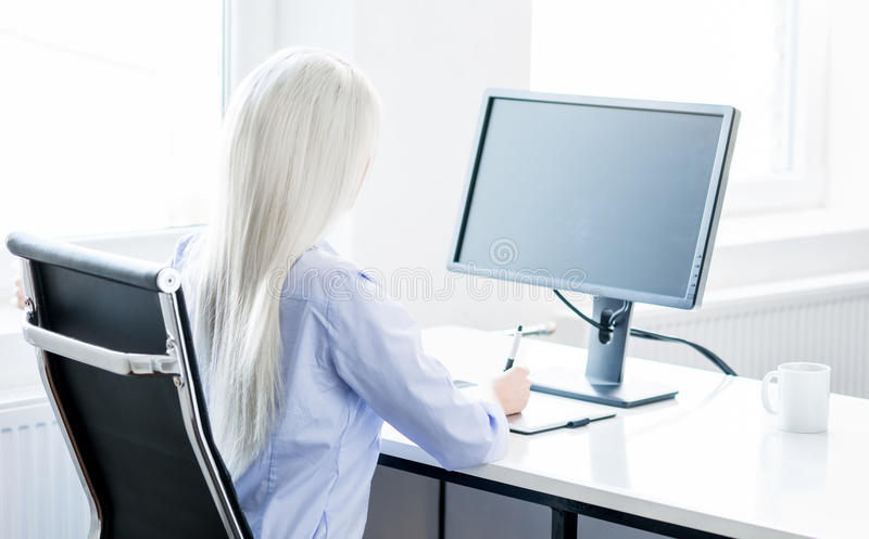 Young woman working on the computer in the office. Digital artist at work. Young and attractive woman working in office. Retoucher editing photos. Blank monitor royalty free stock image