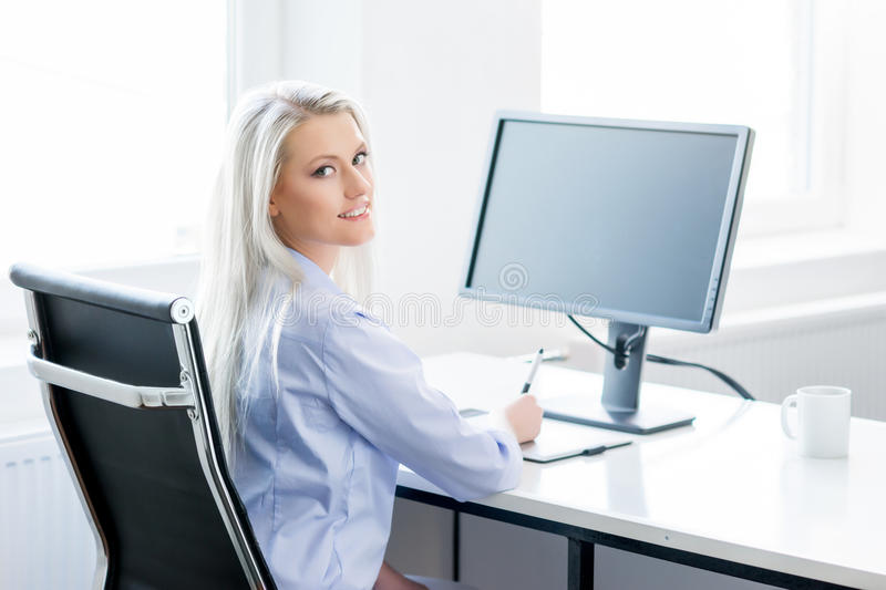 Young woman working on the computer in the office. Digital artist at work. Young and attractive woman working in office. Retoucher editing photos. Blank monitor stock image