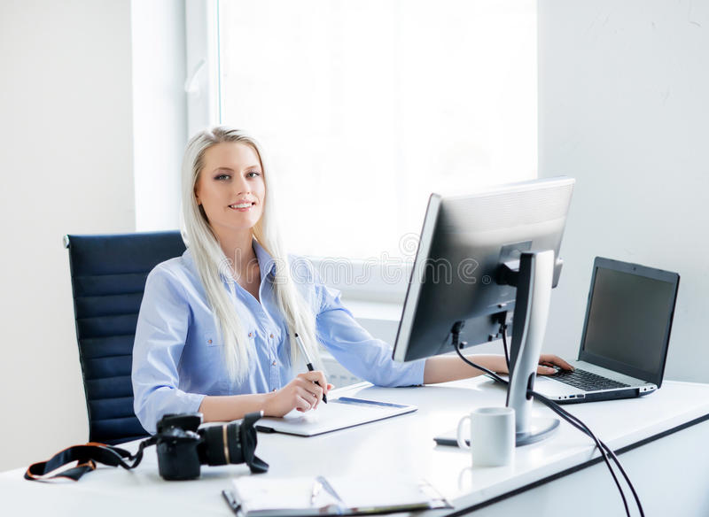 Young woman working on the computer in white office room. Young beautiful woman with pencil working on the computer royalty free stock photography