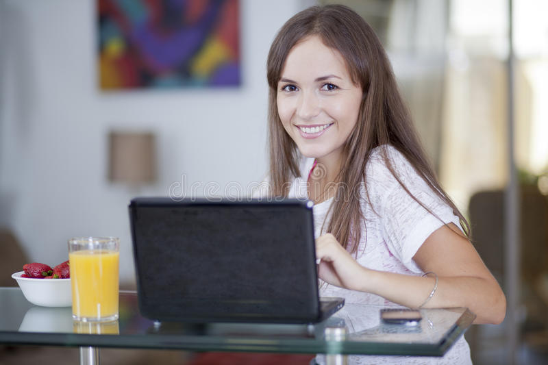 Young woman working from home. Cute girl working in the kitchen and eating breakfast stock photography
