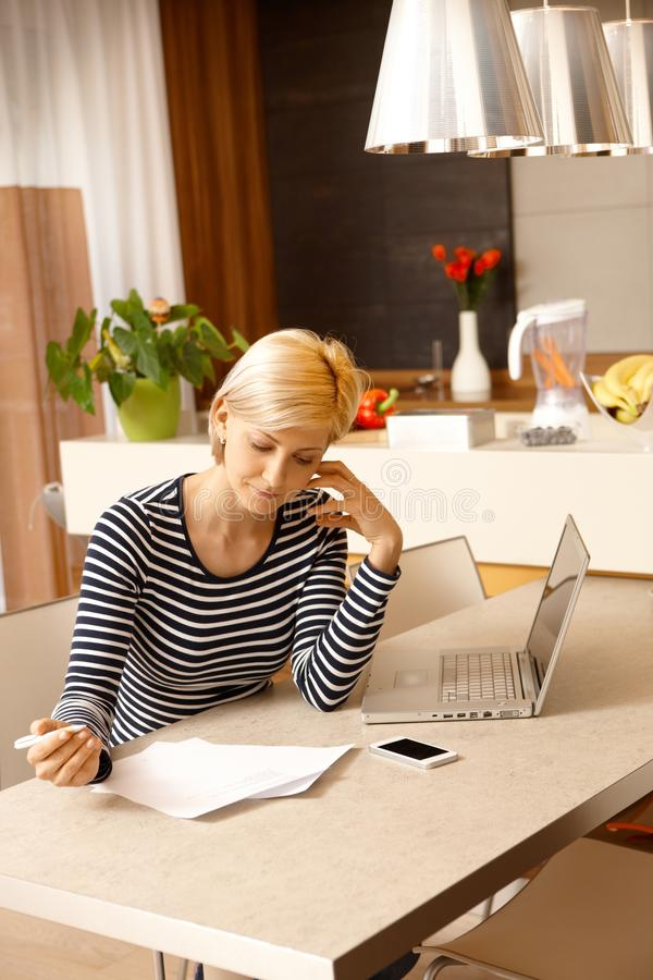 Young woman working at home. Young blonde woman sitting at table, working at home royalty free stock photo