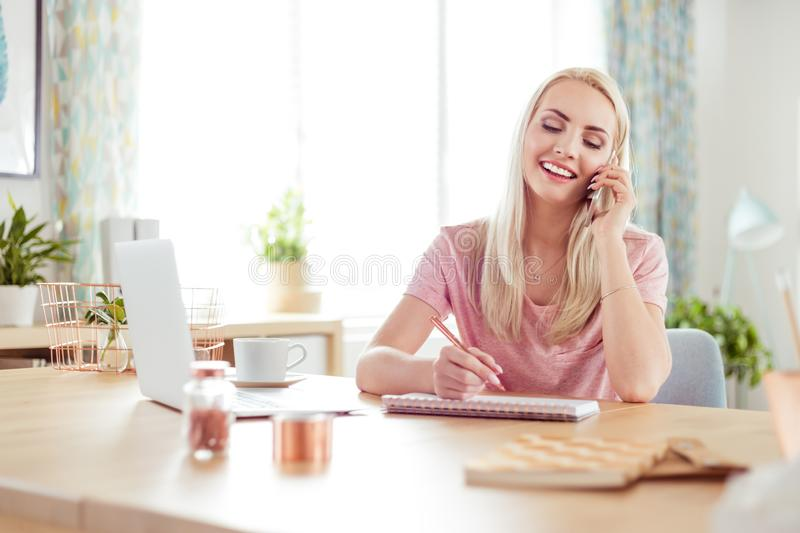 Young woman working at home, talking on mobile stock photos