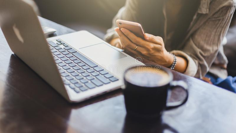 Young woman working on laptop and  coffee cup while sitting at his working place. royalty free stock image