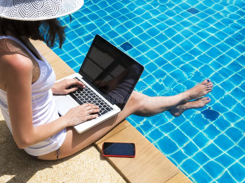 Young woman working on laptop at poolside stock images