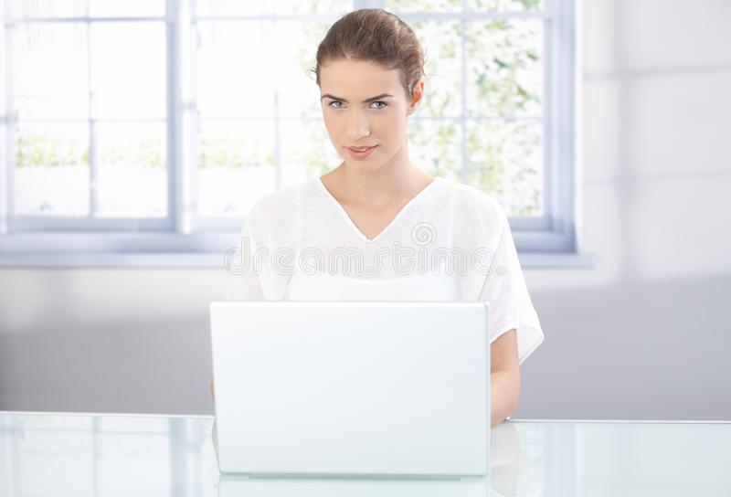 Download Young Woman Working On Laptop At Home Smiling Stock Photo - Image: 23609490