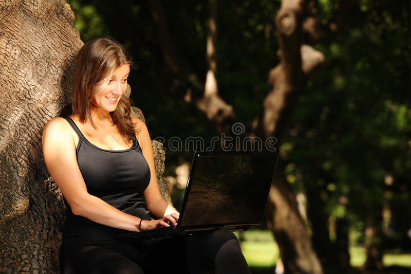 Young woman working on a laptop in the park stock images