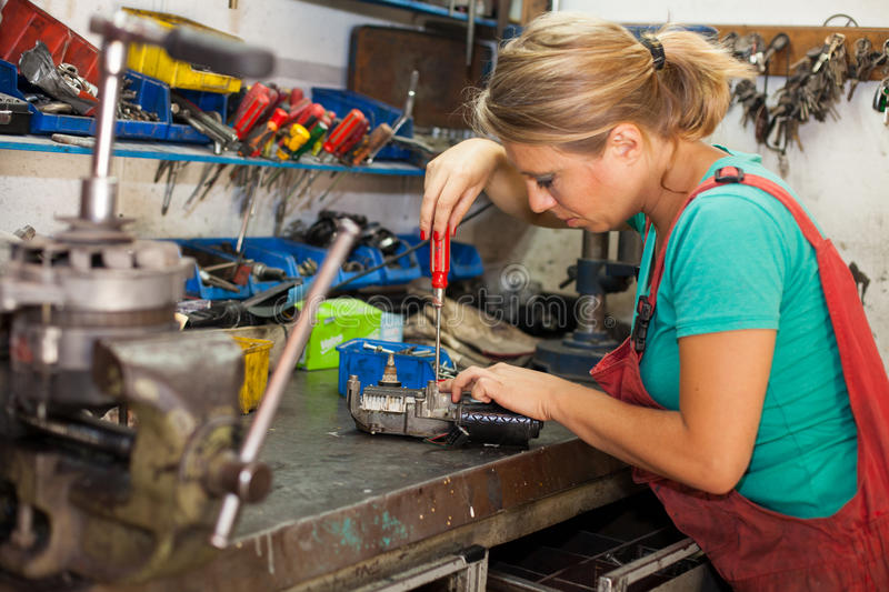 Young woman working in a mechanic shop royalty free stock images