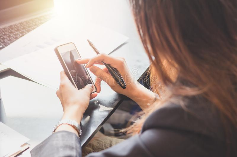 Young woman is working in office,Secretary take notes from the phone,Business young women work on phones and notebooks. People, smartphone, person, female royalty free stock photos