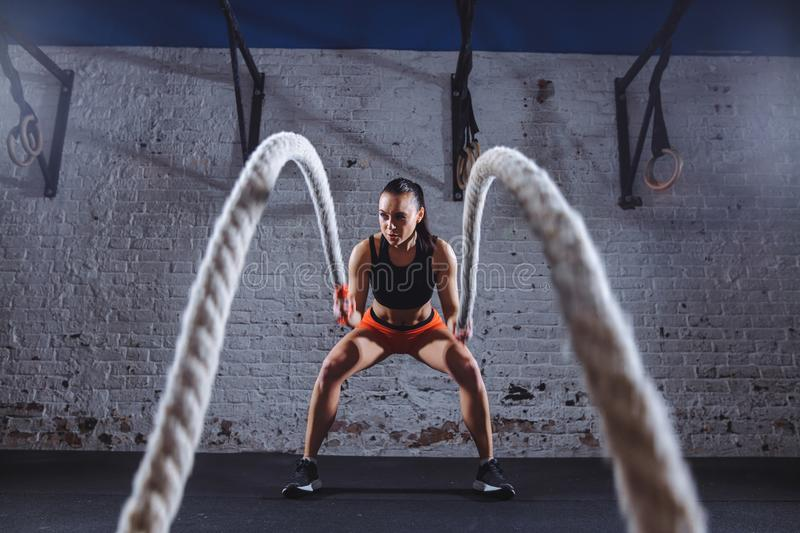 Young woman working out with battle ropes in cross fit gym. Front view of Young woman working out with battle ropes in cross fit gym stock images