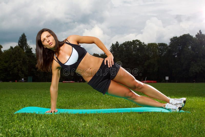Young woman working out in a park royalty free stock photo