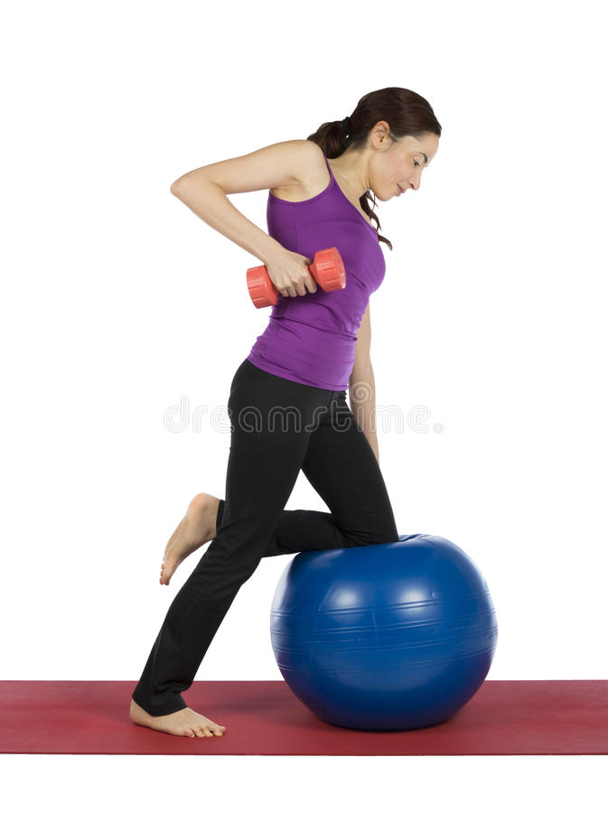 Young woman working out with a pilates ball and a dumbbell stock photography
