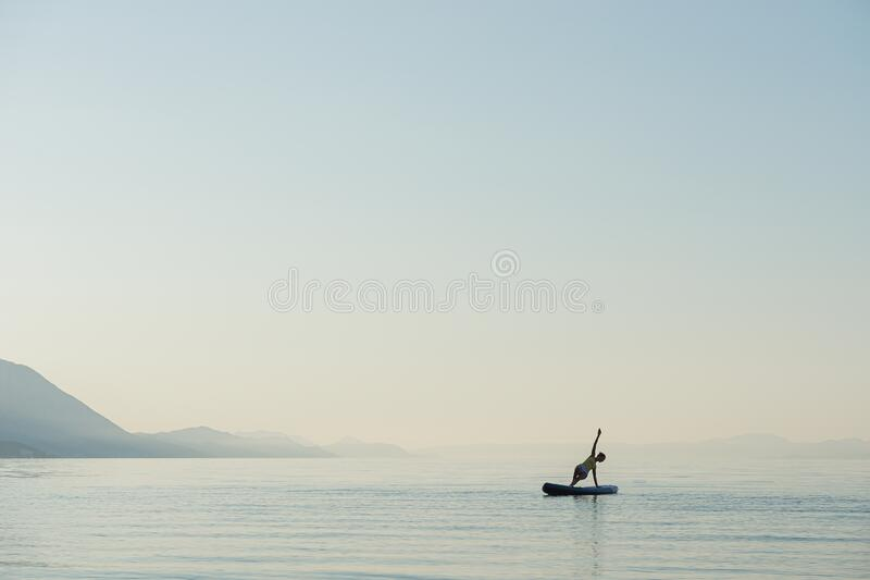 Young woman in yoga pose on sup board royalty free stock images