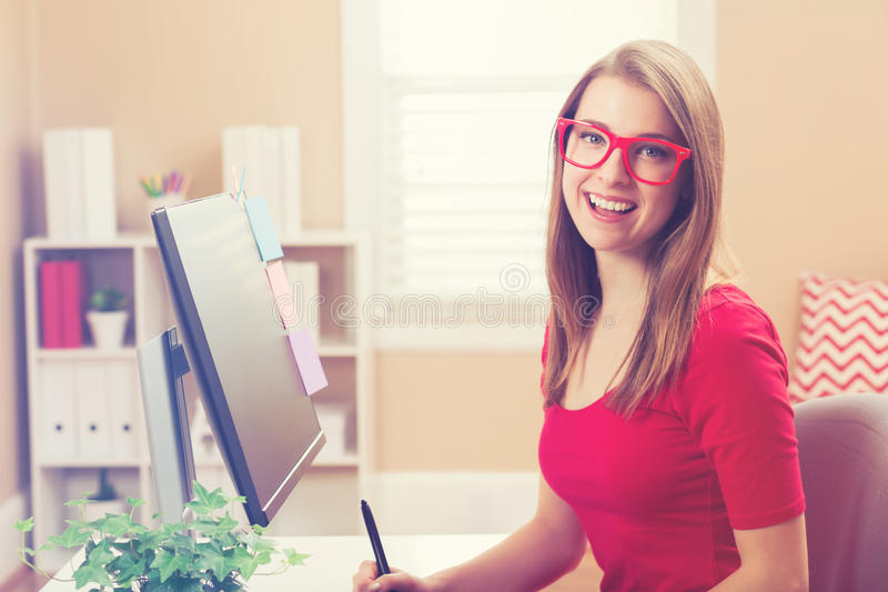Young woman working with a pen tablet in her home office royalty free stock images