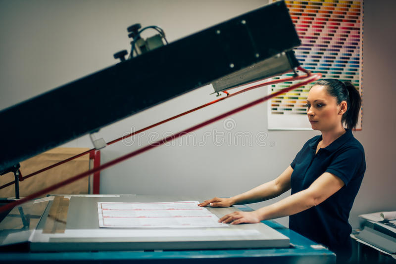 Young woman working in printing factory stock image