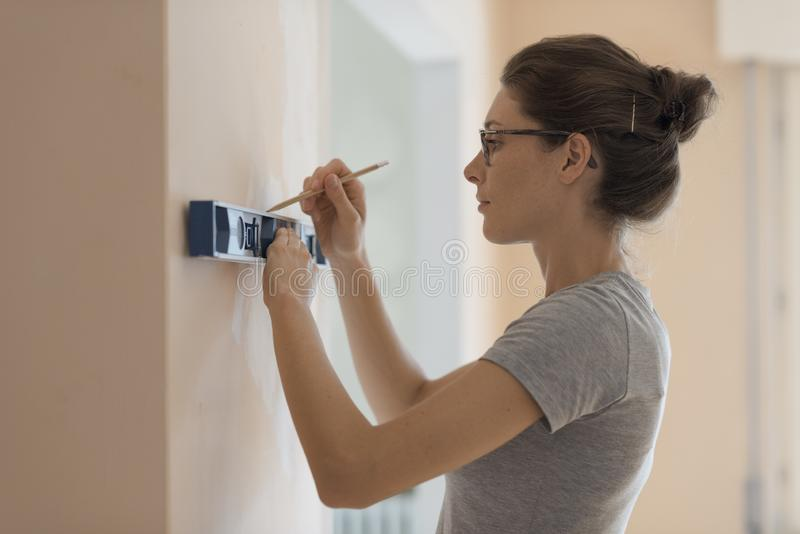 Woman working with a spirit level royalty free stock image
