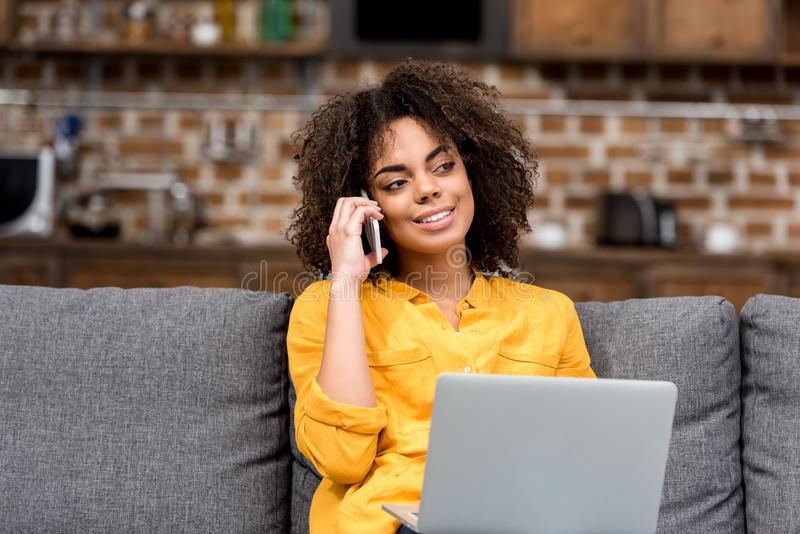 Young woman working and talking by phone at home. On couch stock image