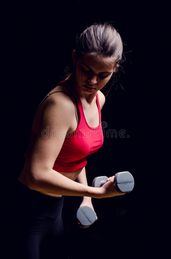 Young woman using dumbbells royalty free stock photos