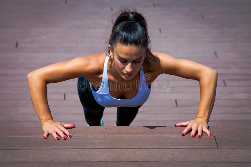 Woman workout push -ups summer day in the city on stairs. Young woman workout push -ups summer day in the city on stairs royalty free stock images