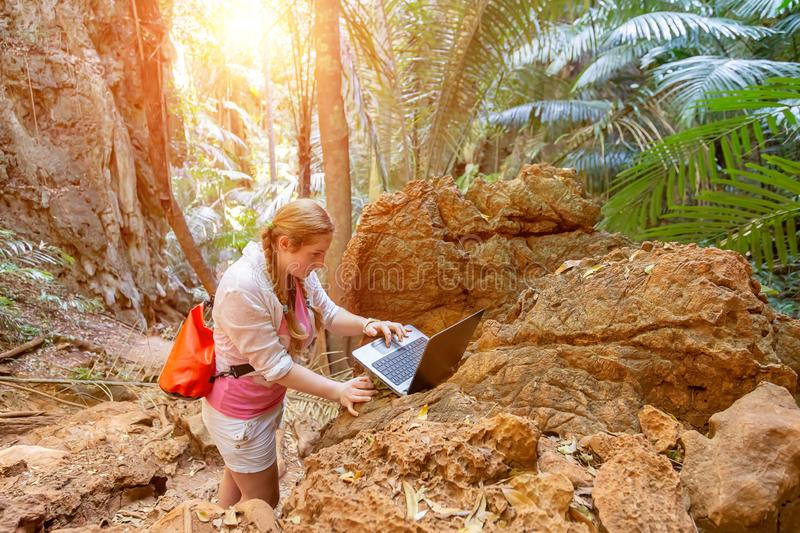 A young woman works with a laptop in the mountains and tropical thickets. Remote work in travel.  Looks at the computer. stock images