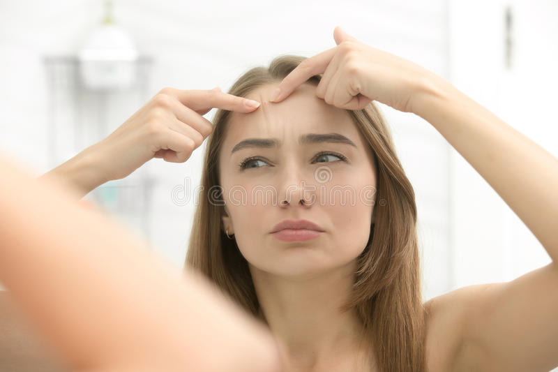 Young woman worried checking wrinkles on her forehead. Young woman worried checking acnes on her forehead, looking at the bathroom mirror. View over the shoulder stock image
