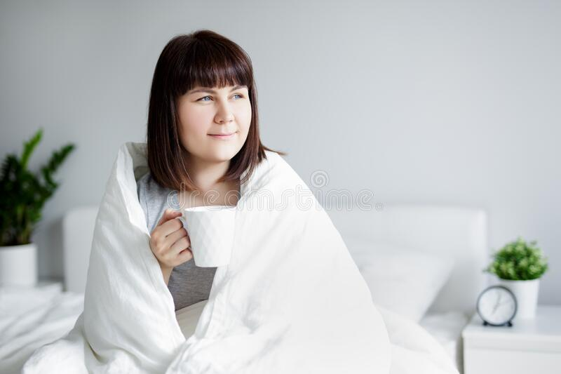 Young woman wrapped in blanket sitting in bed, drinking coffee and thinking or dreaming about something at home royalty free stock photo