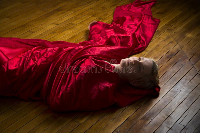 Young woman wrapped in red fabric lying on studio floor. stock photo