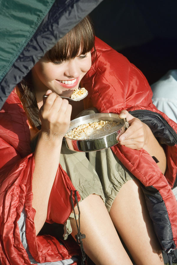 Young woman, wrapped in red sleeping bag, sitting in tent on camping trip, eating cereal, smiling, close-up royalty free stock photo
