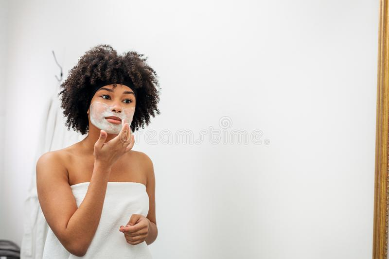 Young woman wrapped in white towel applying natural mask stock images