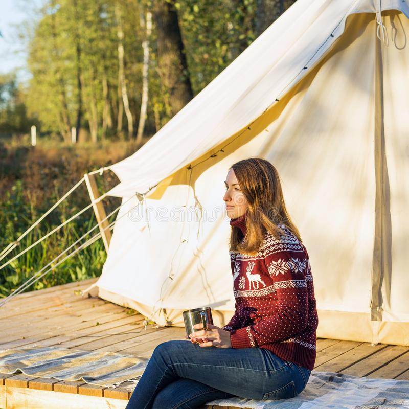 Young woman wraps blanket over herself while drinking coffee near canvas bell tent royalty free stock photography