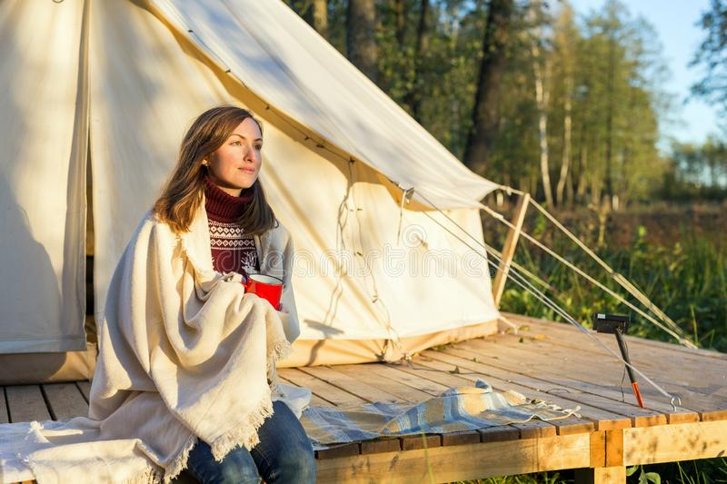 Young woman wraps blanket over herself while drinking coffee near canvas bell tent stock image