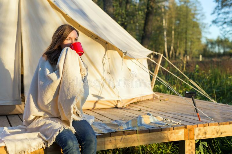 Young woman wraps blanket over herself while drinking coffee near canvas tent in the morning stock images