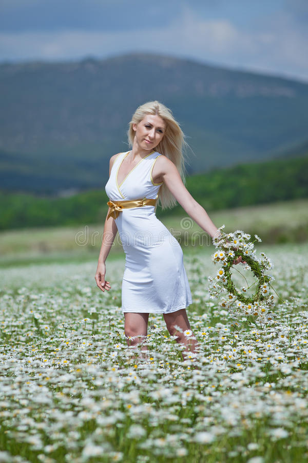 Young woman with wreath on open air. Attractive blonde in chamomile field. Young woman with wreath on open air royalty free stock image