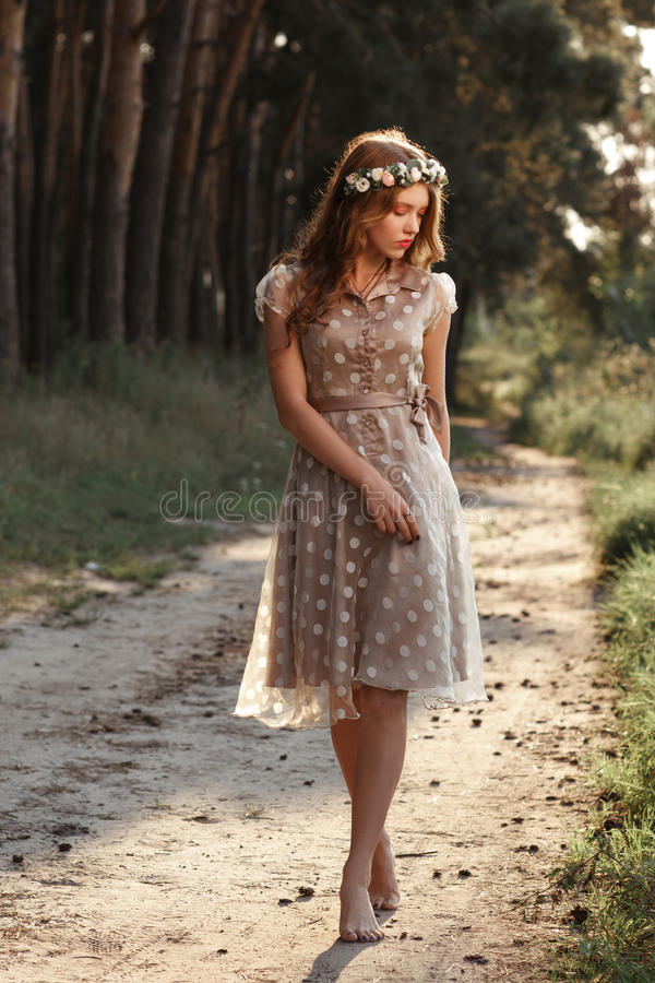 Young woman in wreath walking in forest barefoot stock photo