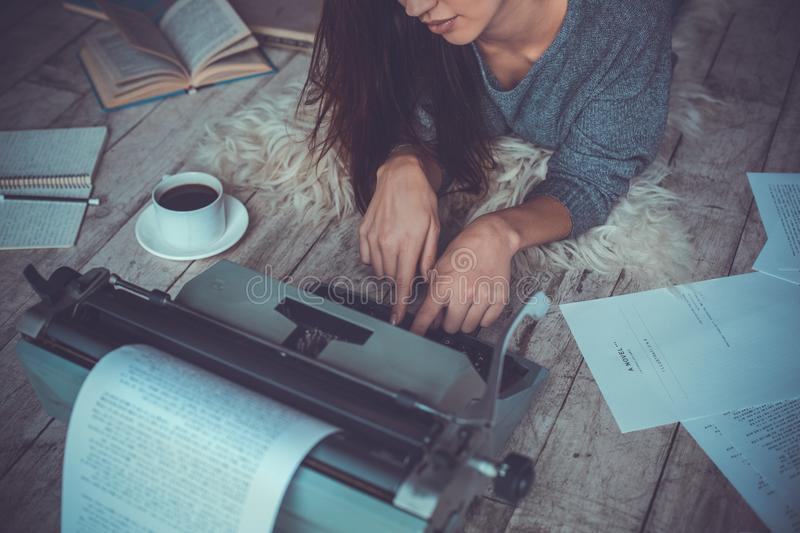 Young woman writer in library at home creative occupation working on typewriter. Young female writer in library indoors working on typewriter writing book close stock images