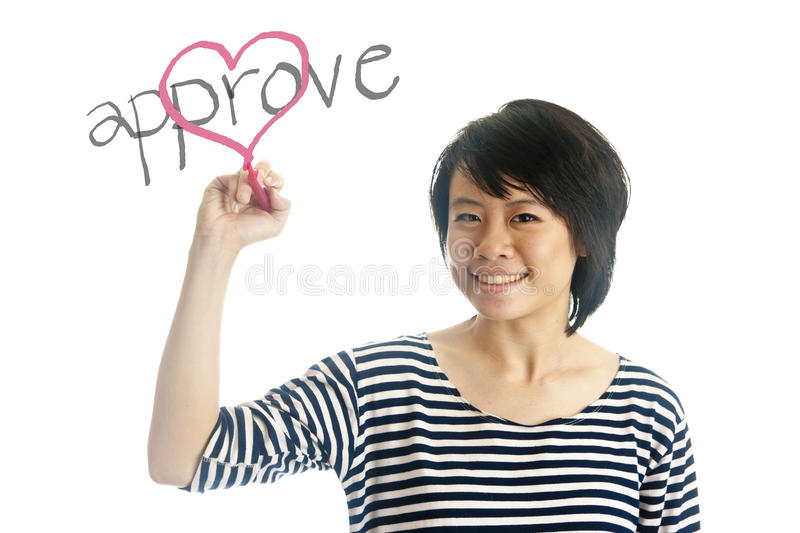Young woman writes approve her heart. Asian young woman writes approve her heart, isolated royalty free stock image
