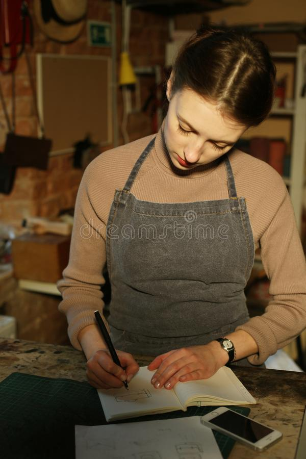 Young woman writes to notebook in sewing workshop, handmade concept. Close up royalty free stock photography