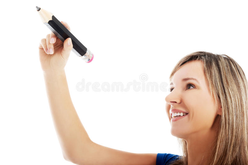 Young woman writing on copy space with big pencil. royalty free stock images