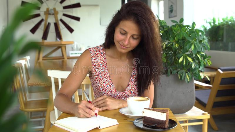 Young woman writing diary in her journal and drink coffee stock images
