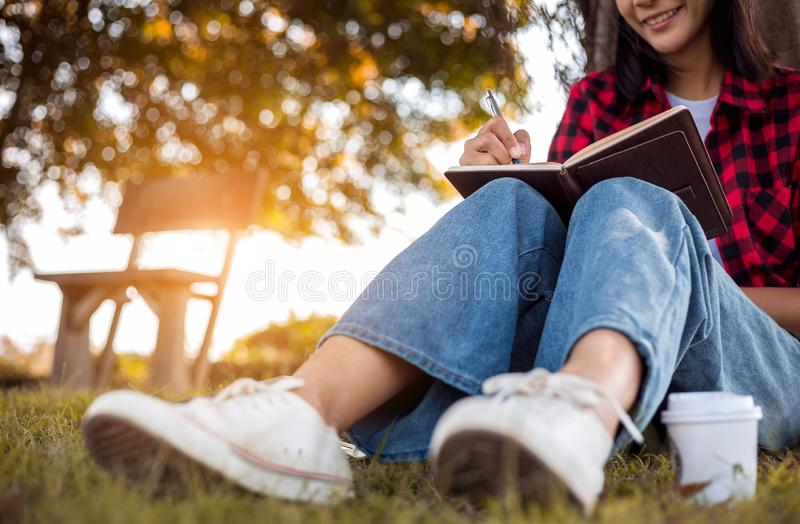 Young woman is writing diary, sitting under tree in park. College student is writing note stock photos