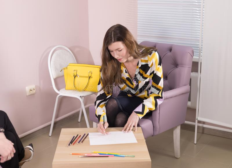 Young woman writing down a note with colour pencils sitting in the armchair at the doctor`s office. Front view royalty free stock photos