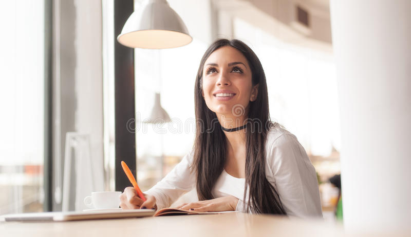 Young woman writing in her notebook and drinking morning coffee stock photo