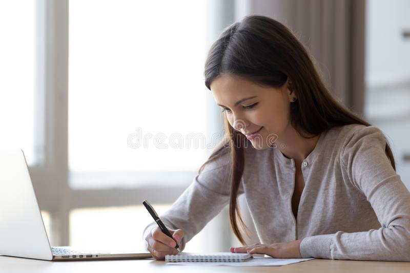 Young woman writing notes in notebook making list planning tasks. Young professional woman intern student noting in notebook studying at home office, teen girl stock images
