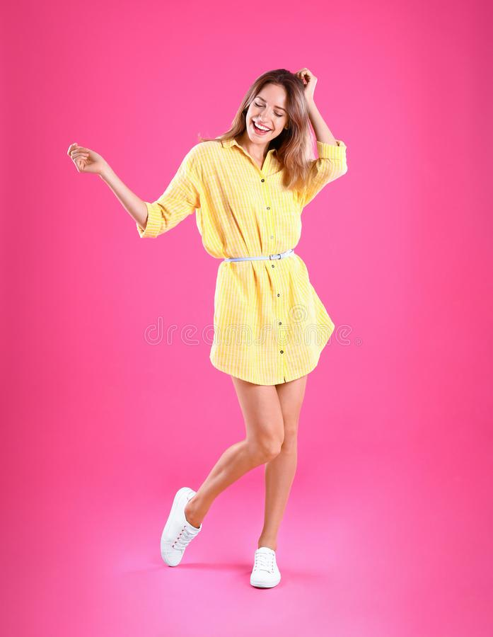 young woman in yellow dress dancing on pink background royalty free stock photography