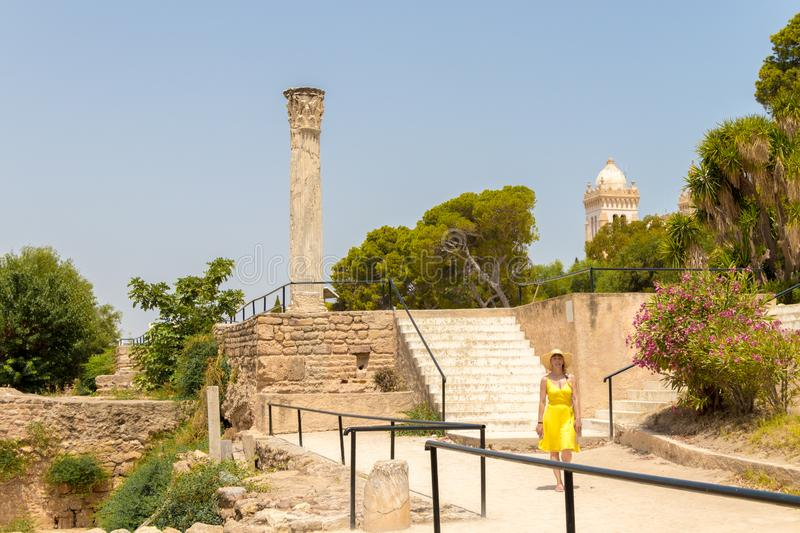 Young woman in yellow dress in front of the Carthage ancient ruins, Tunis, Tunisia.  stock photos